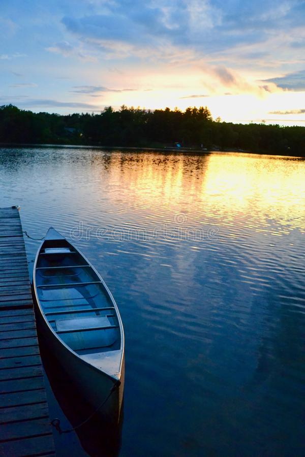Заход солнца, каное, и спокойное озеро стоковая фотография