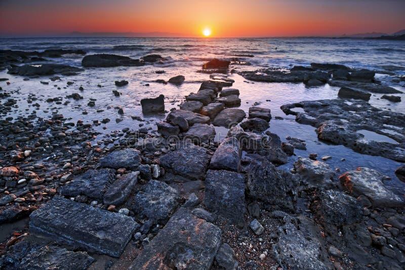 Заход солнца лета на скалистом пляже в древнем городе стороны в Анталье стоковые изображения rf