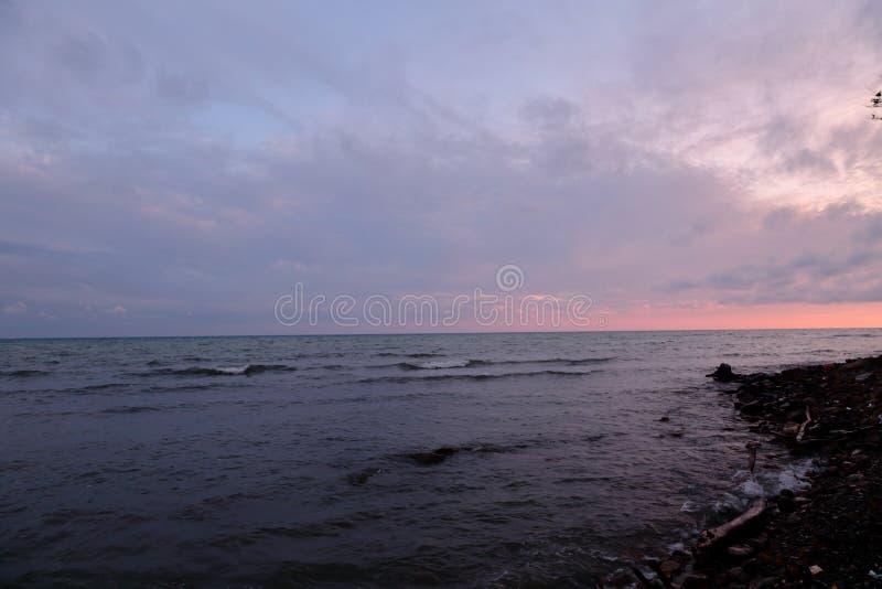 Заход солнца, лучи ` s солнца делает их путь через тяжелые облака и освещает лето, побеспокоенное море стоковые изображения rf