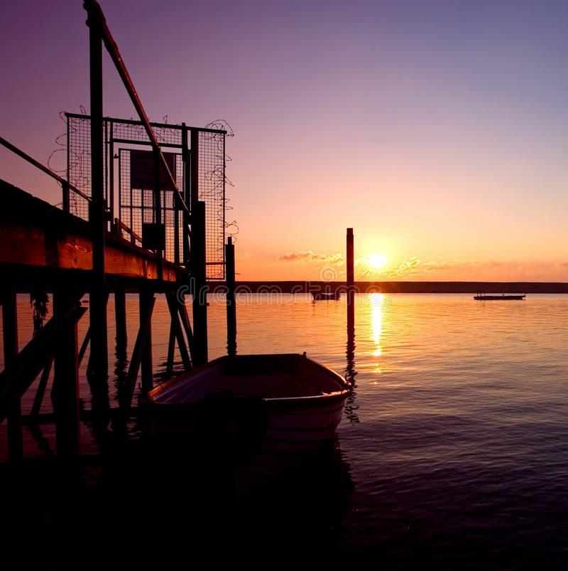 заход солнца моря rowing boaton старый стоковая фотография