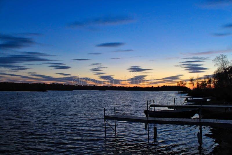 Заход солнца над большим озером и доками выступающими в воду расположенную в Hayward, Висконсине стоковое фото rf