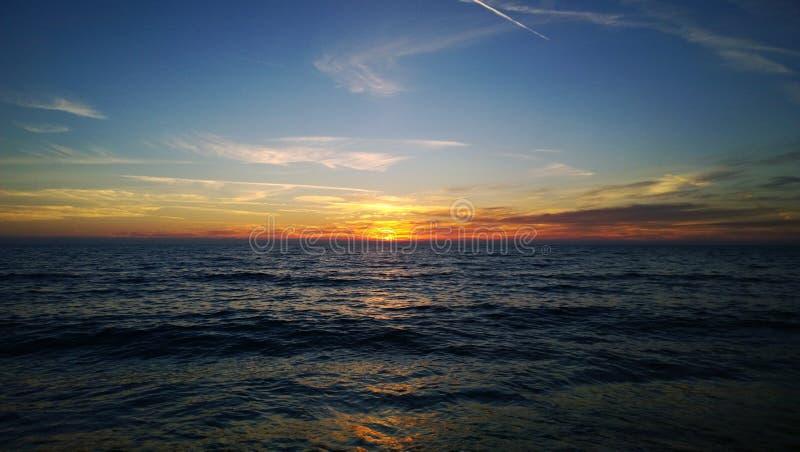 Заход солнца над вечером осени моря теплым - покрашенными лучами солнца, отражением на воде, некоторых облаках стоковое фото rf