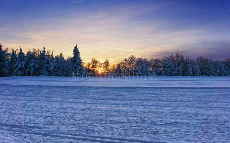 Заход солнца над выхоленными следами лыжи по пересеченной местностей стоковые фото