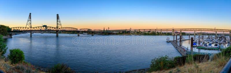 Заход солнца над горизонтом города Портленда Орегона вдоль портового района реки Willamette стоковое изображение