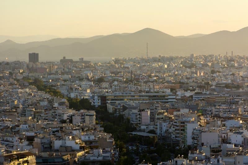 Заход солнца над городом, городом в желтом солнечном свете, Афинами стоковые фото