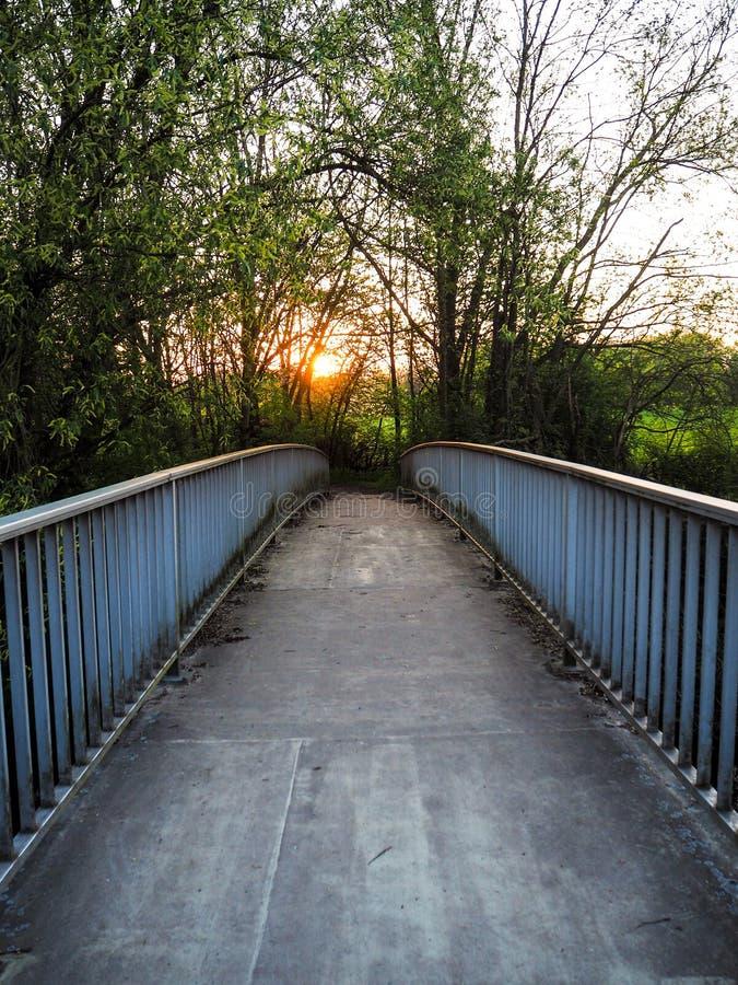 Заход солнца над дезертированным мостом металла пересекая реку Leine внутри стоковые изображения