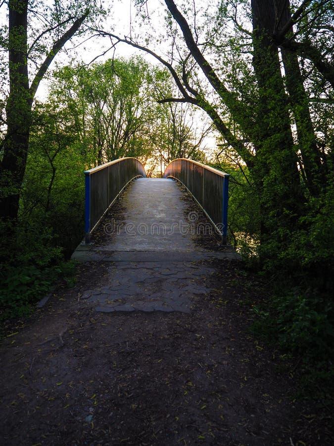 Заход солнца над дезертированным мостом металла стоковые изображения