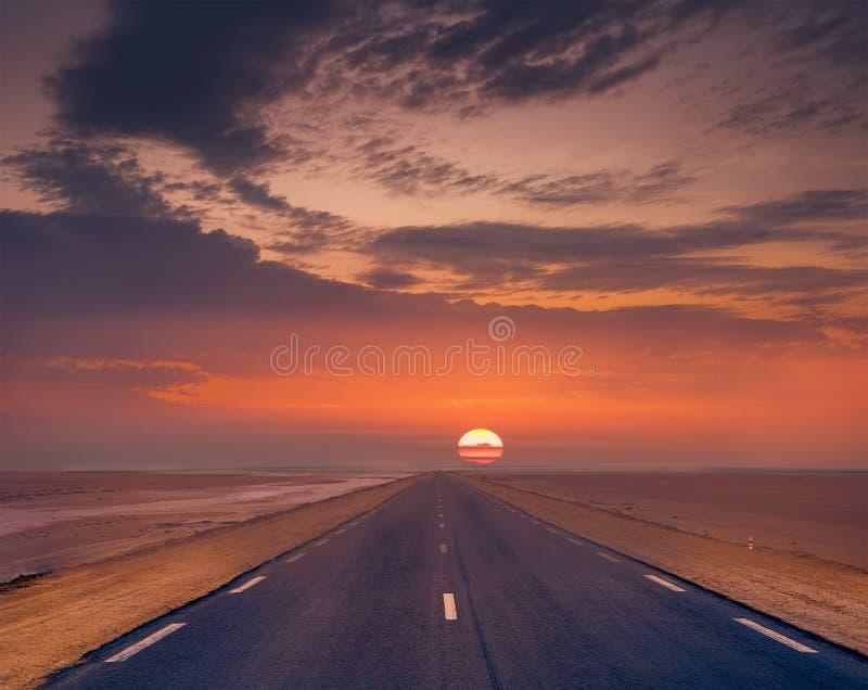 Заход солнца над дорогой пустыни стоковое изображение