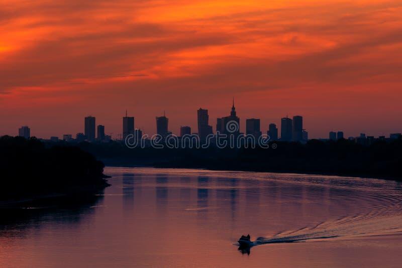Заход солнца над зданиями города Варшавы Рекой Висла в Польше стоковая фотография