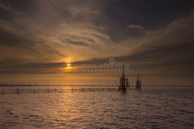 Заход солнца над озером с драматическим небом стоковые фото