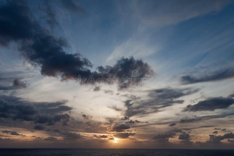 Заход солнца над океаном с темными облаками стоковая фотография rf