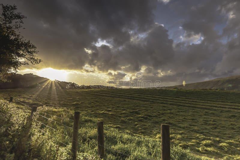 Заход солнца над полем и драматическим небом в районе озера, Cumbria, Великобритании стоковая фотография rf