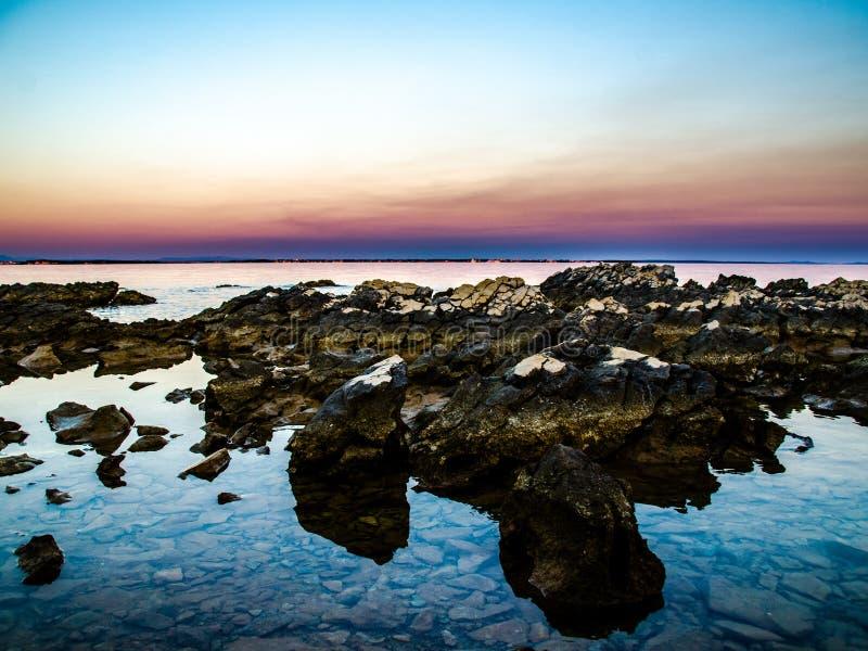 Заход солнца над скалистым пляжем стоковое изображение