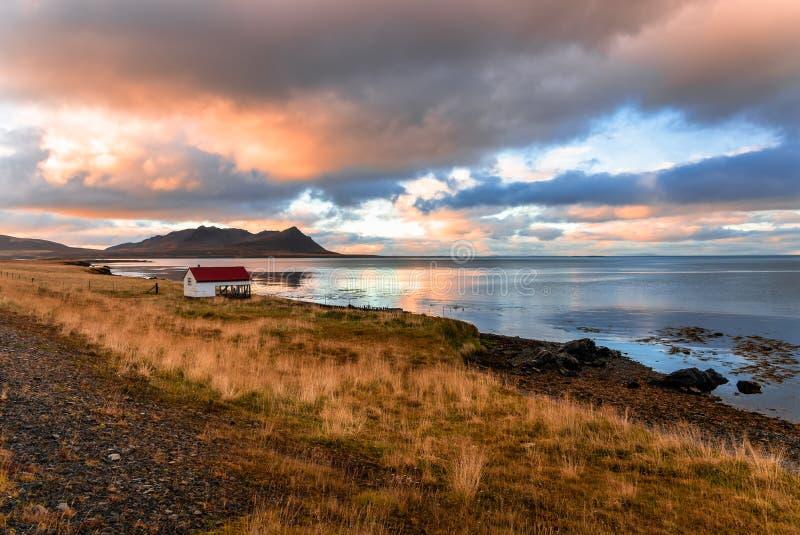 Заход солнца над удя сараем на скалистом побережье в Исландии стоковые изображения