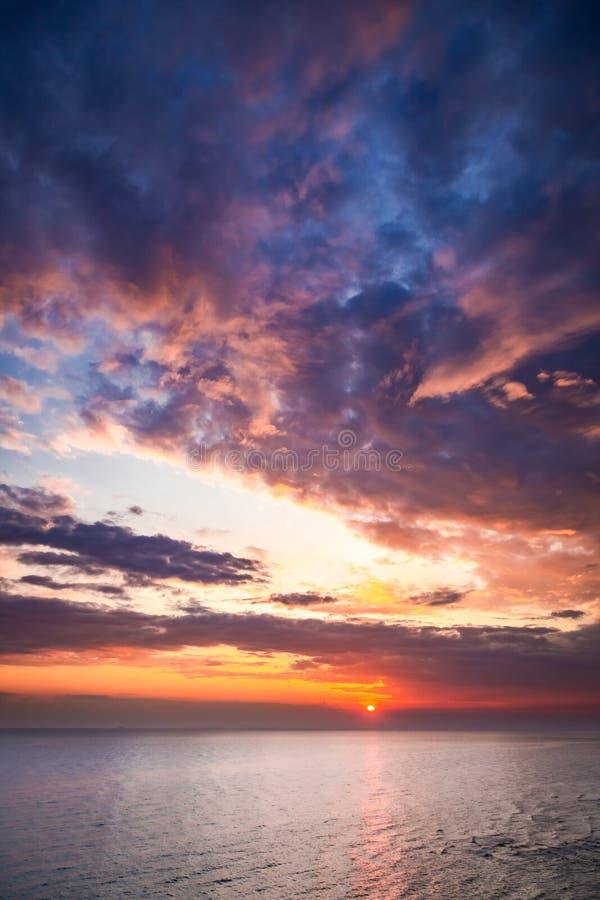 Заход солнца над штилем на море в лете с лучем солнца стоковые изображения rf