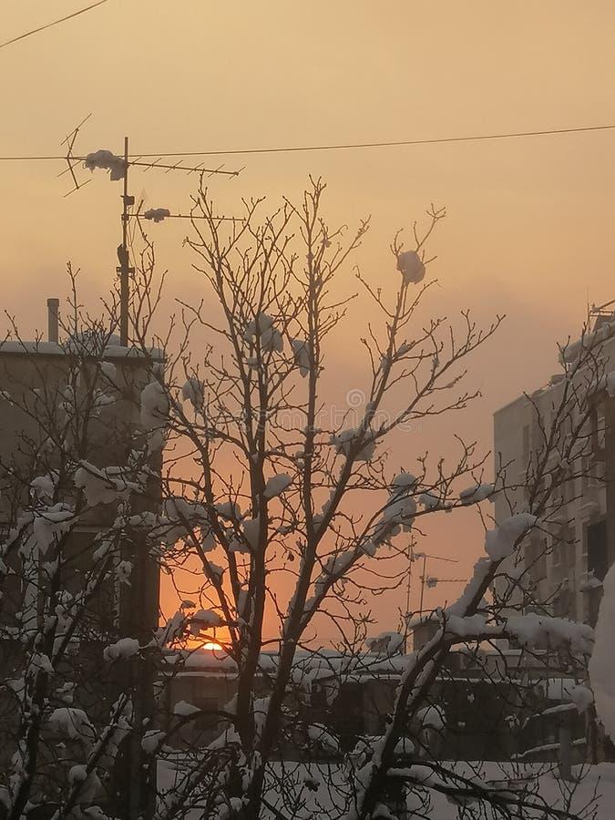 Заход солнца на день снега в городке стоковые изображения