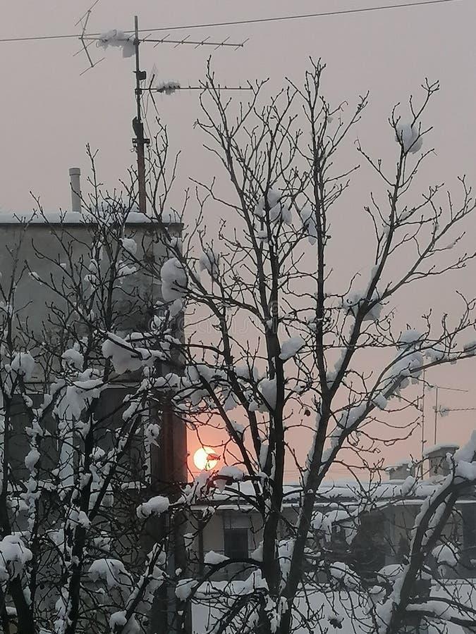 Заход солнца на день снега в городке стоковое фото