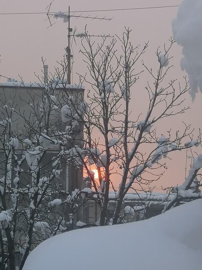 Заход солнца на день снега в городке стоковые изображения rf