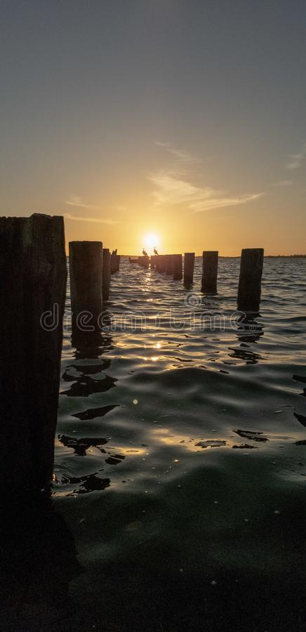 Заход солнца на Мексиканском заливе перед сломленной пристанью стоковые изображения