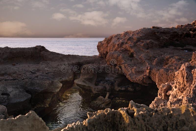 Заход солнца на море на зимний день, лучи солнца ломает вниз на утесах стоковое фото