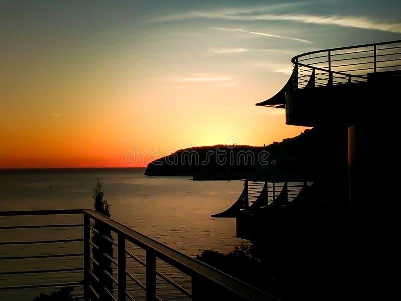 Заход солнца на море со сценарными облаками на горизонте стоковая фотография