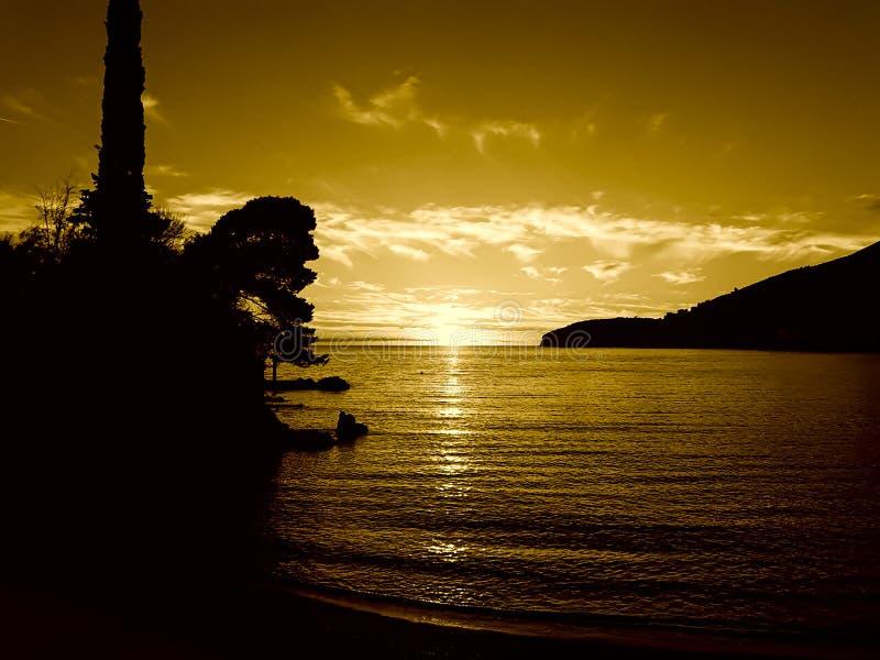 Заход солнца на море со сценарными облаками на горизонте стоковое изображение rf