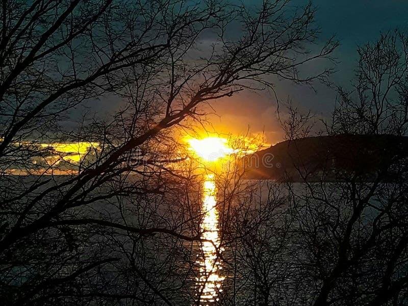 Заход солнца на море со сценарными облаками на горизонте стоковое фото