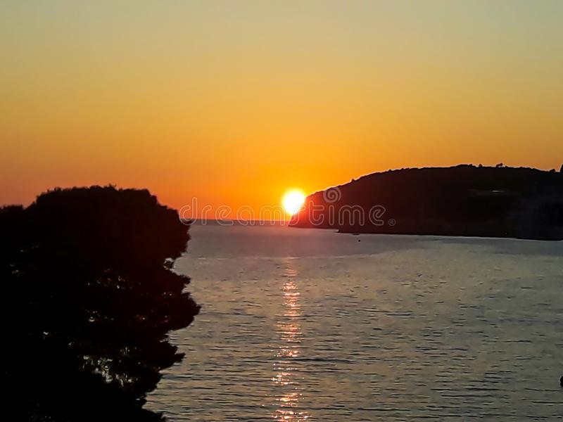 Заход солнца на море со сценарными облаками на горизонте стоковые фото