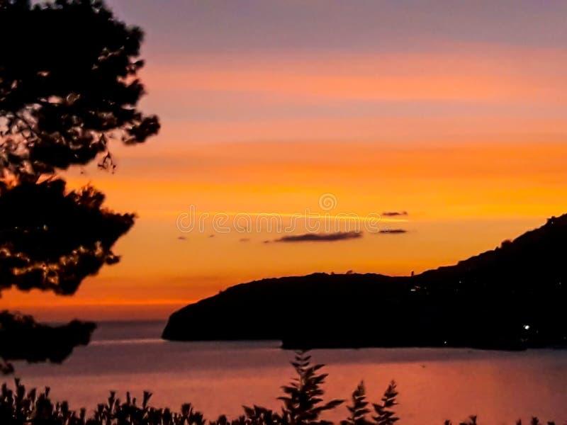 Заход солнца на море со сценарными облаками на горизонте стоковые изображения