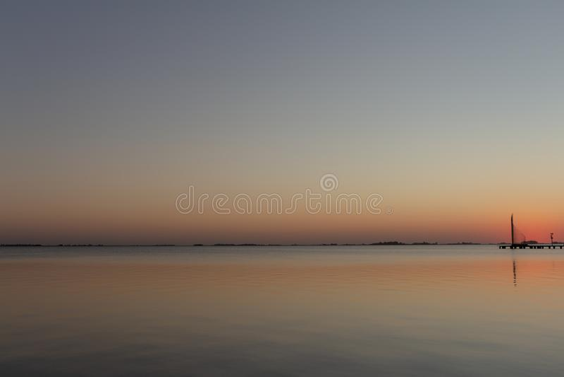 Заход солнца на озере Солнце отражает свой свет на озере Оранжевые и голубые цвета преобладают сцену стоковая фотография rf