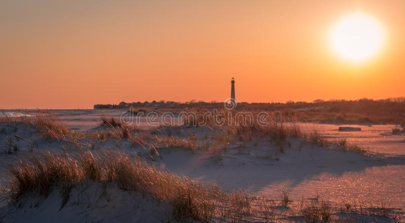 Заход солнца на пляже как маяк Cape May стоит на заднем плане на самой южной подсказке NJ стоковые изображения rf