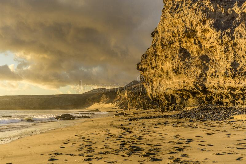 Заход солнца на пляже Фуэртевентуры с лавой трясет стоковые изображения