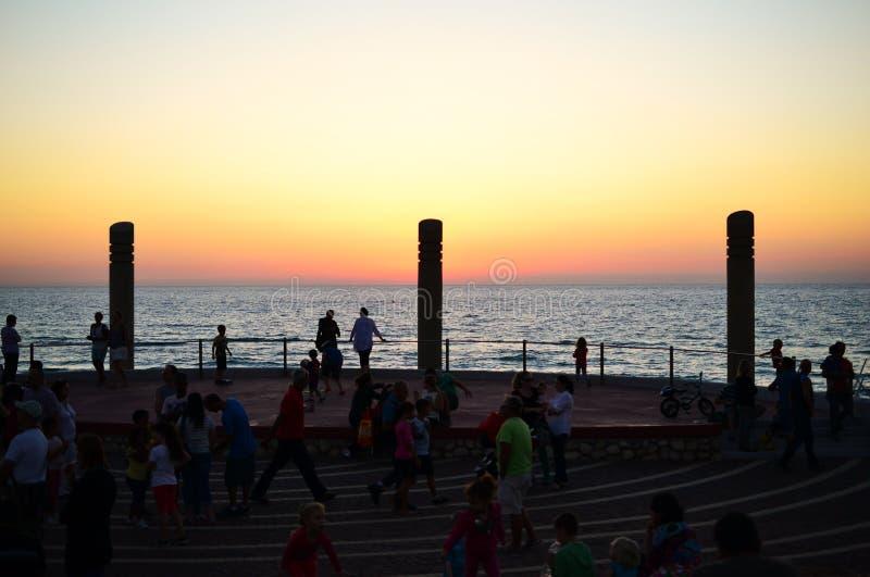 Заход солнца на пляже Carmel, Dado Hof, штендерах и квадрате, городе Хайфы, центре города, Израиле стоковые фото