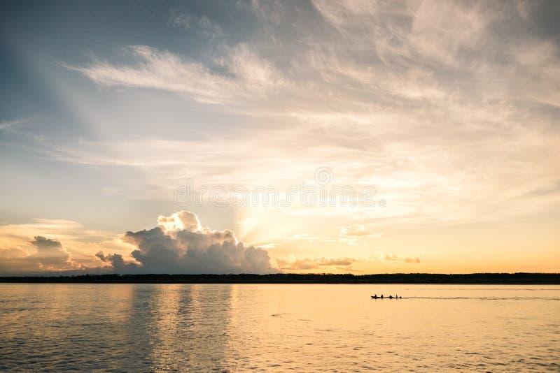 Заход солнца на реке Javari с хряком проходя мимо стоковая фотография rf