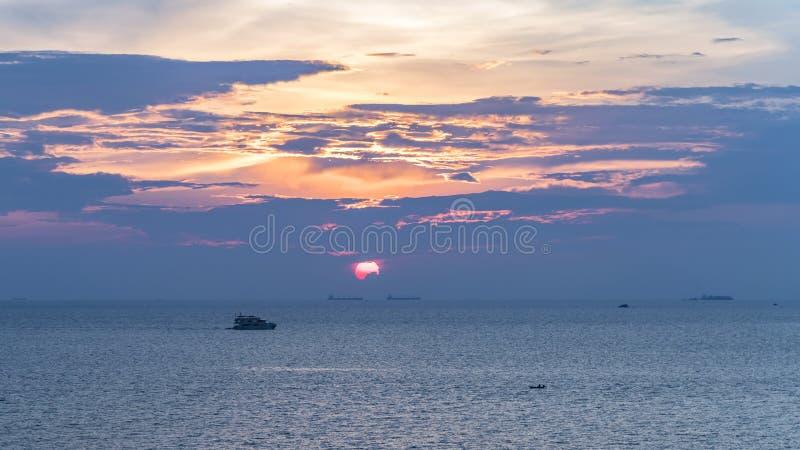 Заход солнца на сумраке, там малые и большие шлюпки в изображении стоковые фото
