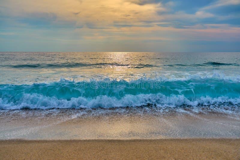 Заход солнца на тропическом пляже, солнце за облаками отражает на воде стоковые фото