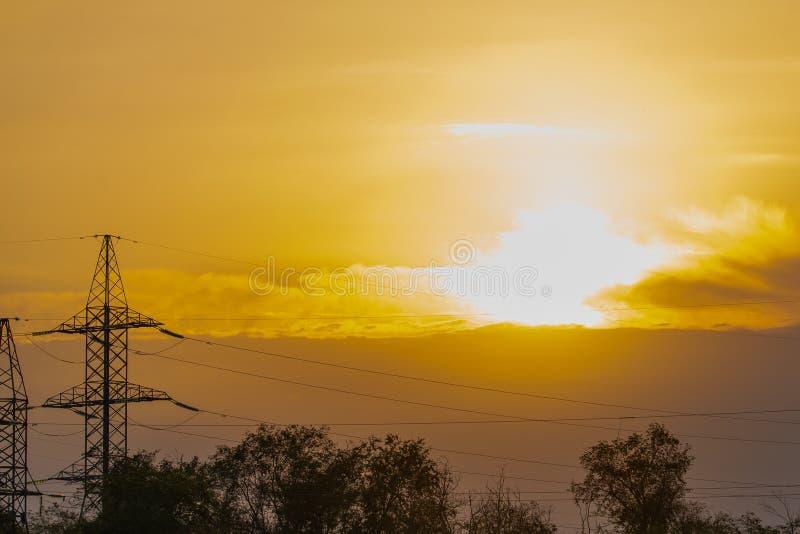Заход солнца огня в облаке Форма высоковольтного поляка и электрические линии с предпосылкой неба захода солнца огня стоковые фото