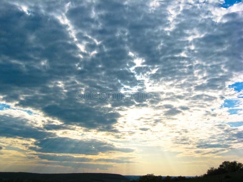 Заход солнца осени Лучи солнца выравниваясь солнца выходят сквозь отверстие облака против голубого неба стоковое фото rf