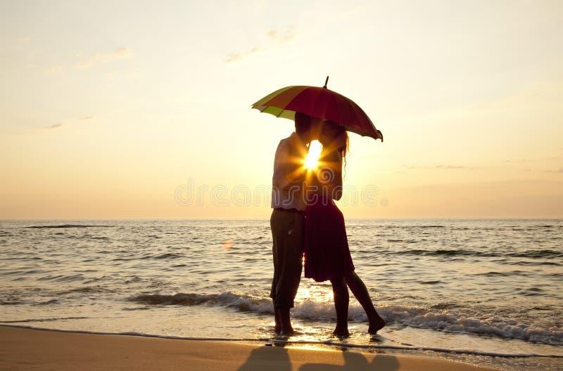 заход солнца пар пляжа целуя стоковое фото rf