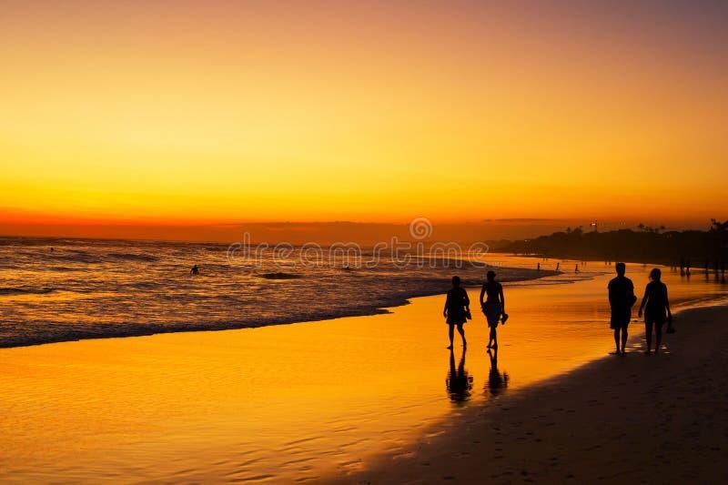 Заход солнца пляжа океана людей идя стоковая фотография rf