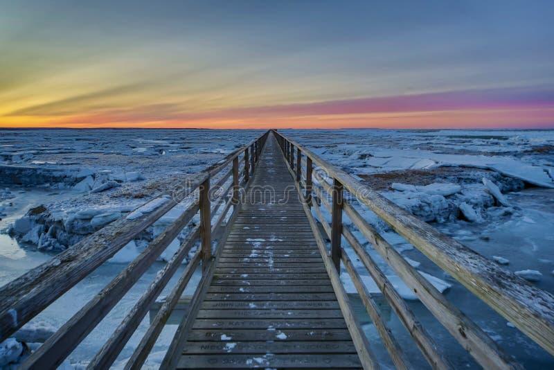 Заход солнца променада на серой треске накидки пляжа ` s стоковое фото