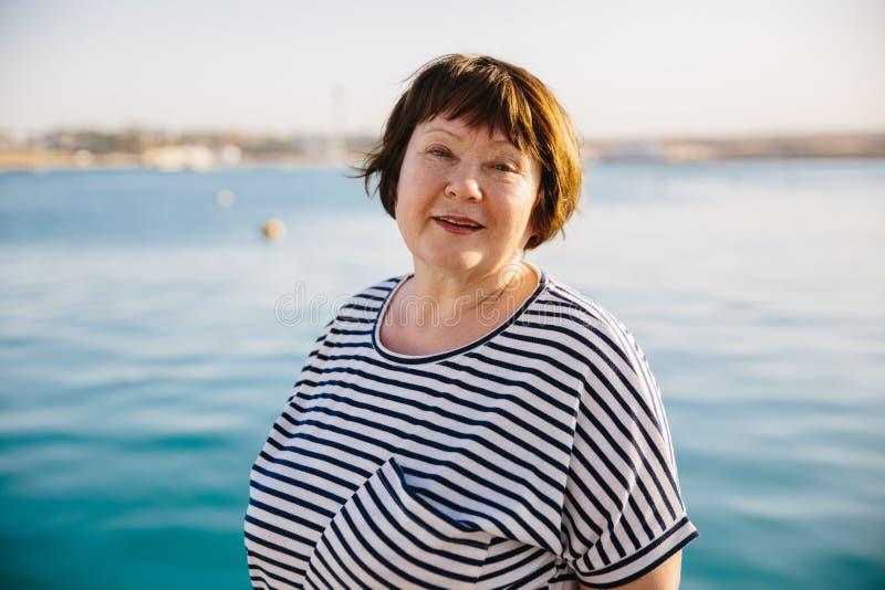 Заход солнца старшей женщины расслабленный и счастливый на море стоковые изображения rf