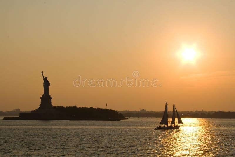 заход солнца статуи вольности стоковая фотография rf