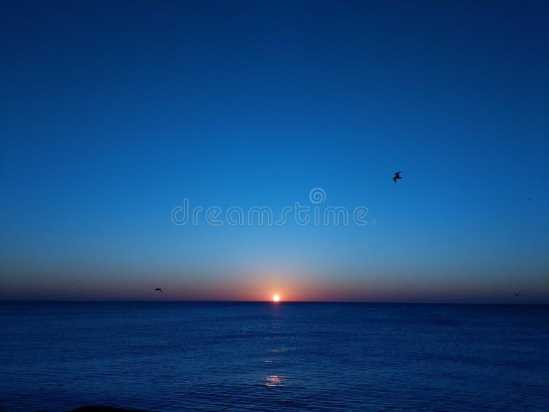Заход солнца стороны моря стоковые фото
