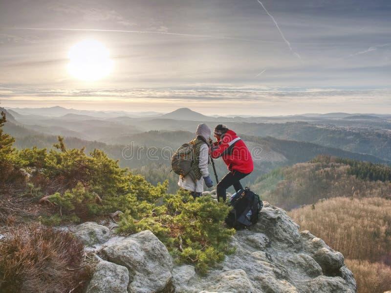 Заход солнца стрельбы человека и девушки на верхней горе стоковое фото