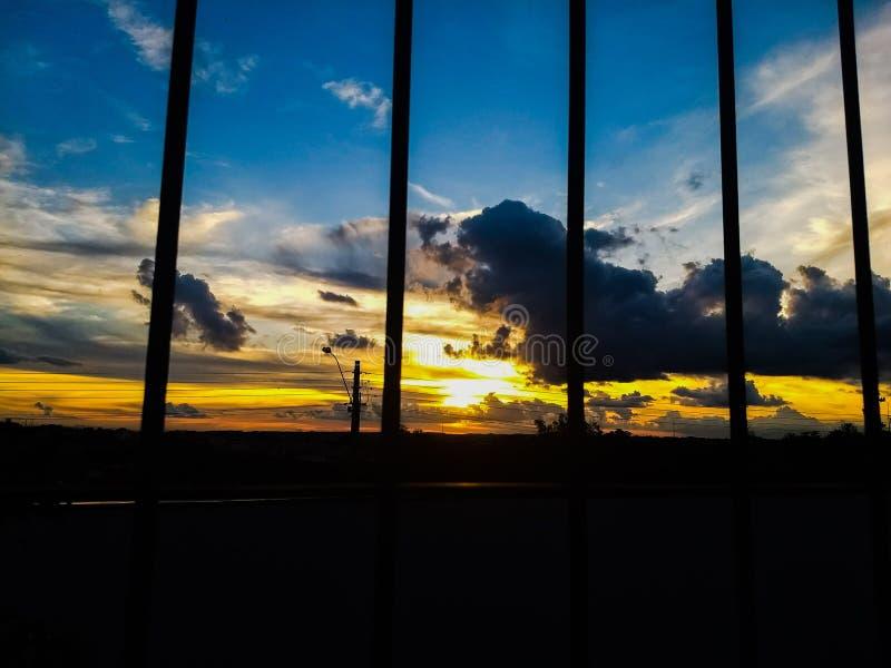 Заход солнца с облаками желтого цвета цвета неба темными и голубыми частями, черной решеткой в фронте стоковая фотография