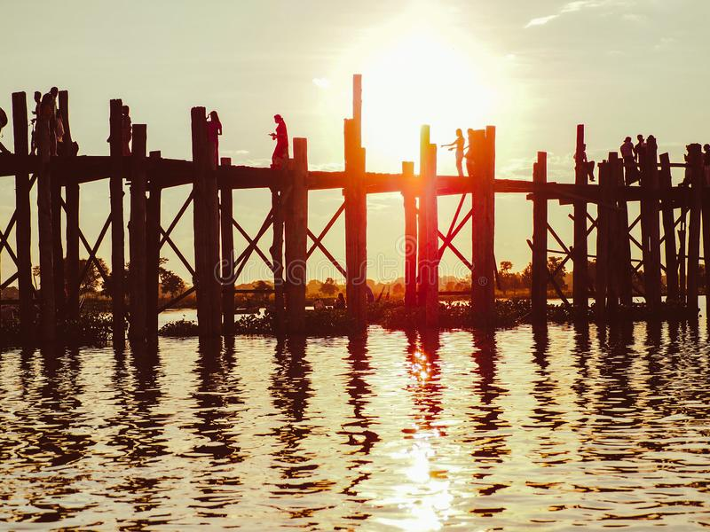 Заход солнца с силуэтом людей идя на мост U-Bein стоковое фото rf