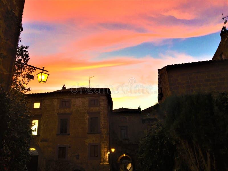 Заход солнца, цвета, розовое небо и сказка в Civita di Bagnoregio, городке в провинции Витербо, Италии стоковое фото rf
