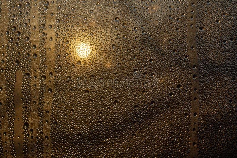Заход солнца через misted стекло с падениями и потеками стоковые изображения rf
