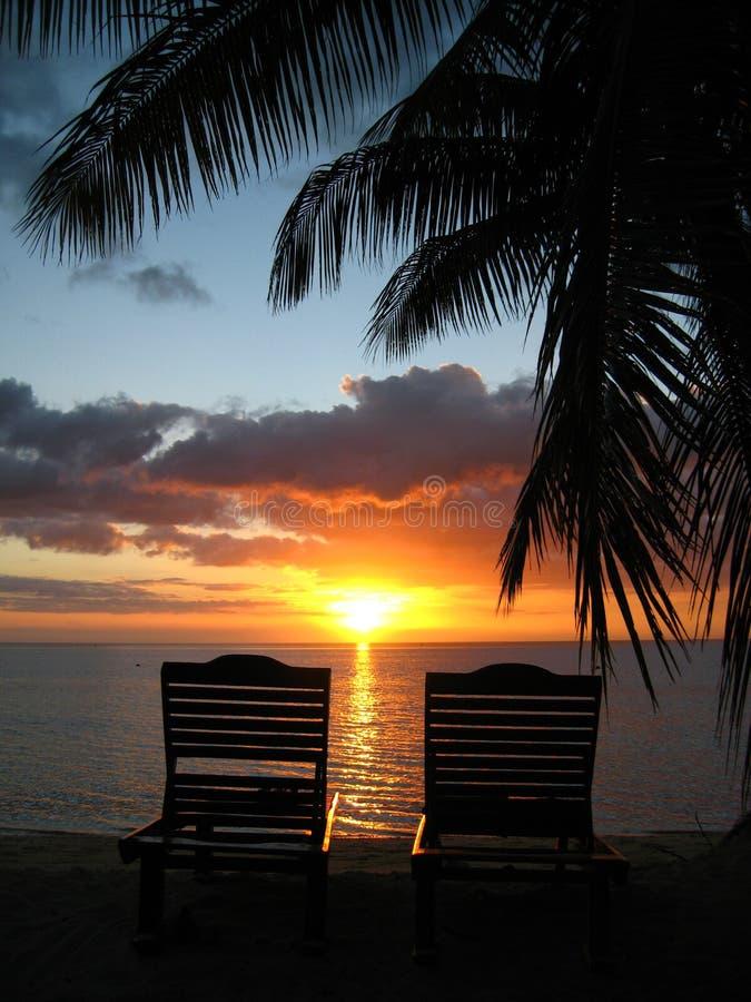 заход солнца 2 deckchairs пляжа стоковые изображения